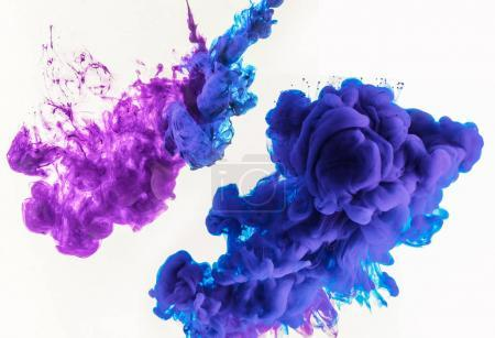 abstract design with smoky splashes of blue and purple paint in water, isolated on white