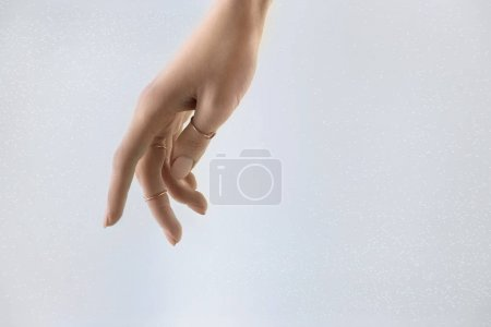 Photo for Cropped view of tender female hand with rings, isolated on grey - Royalty Free Image