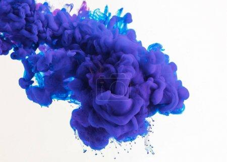 abstraktes Design mit fließender blauer und lila Tinte im Wasser, isoliert auf Weiß