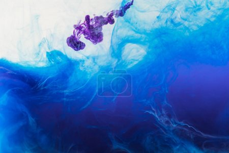 blue and purple paint mixing in water