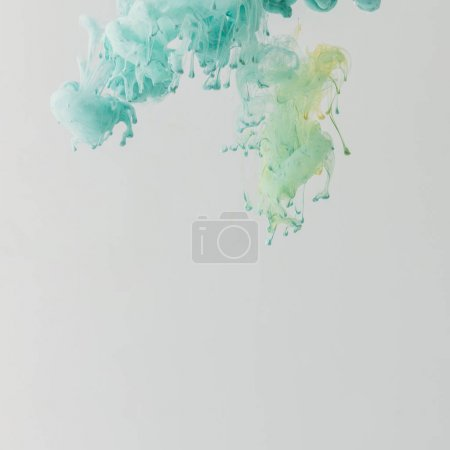 light turquoise paint flowing in water with drops, isolated on grey