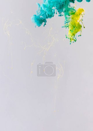 background with turquoise and yellow paint flowing in water with drops, isolated on grey
