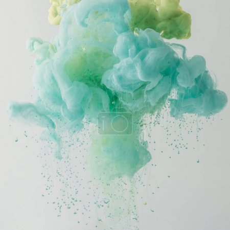 Photo for Artistic background with turquoise paint flowing in water, isolated on grey - Royalty Free Image