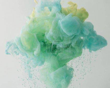 Foto de Textura con fluir luz turquesa pintura en agua con gotas, aislado en gris - Imagen libre de derechos