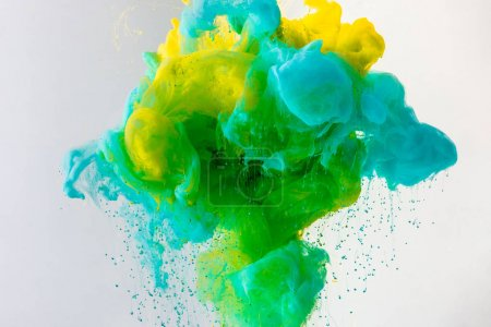 wallpaper with flowing turquoise, yellow and green paint in water, isolated on grey