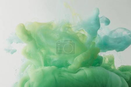 Photo pour Texture légère avec coulée turquoise et peinture verte dans l'eau, isolée sur gris - image libre de droit