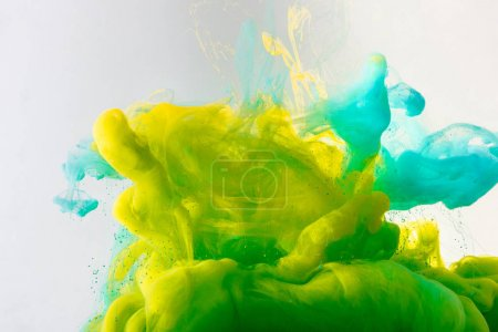design with flowing turquoise, yellow and green paint in water, isolated on grey