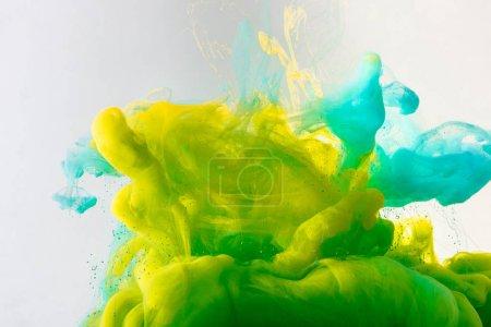 conception avec fluide turquoise, jaune et vert de peinture à l'eau, isolé sur fond gris