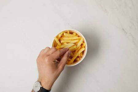 Photo for Top view of man taking french fries from bowl on white - Royalty Free Image