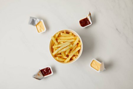 top view of tasty french fries in bowl surrounded with containers of sauces on white