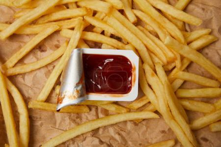 top view of french fries on crumpled paper with container of ketchup