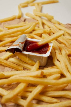 french fries on crumpled paper with container of ketchup