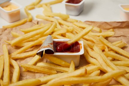 close-up shot of french fries on crumpled paper with containers of sauces