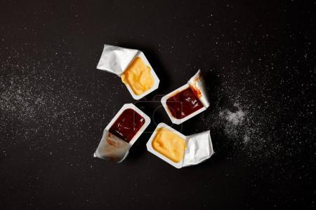 Photo for Top view of plastic containers with sauces on black surface spilled with salt - Royalty Free Image
