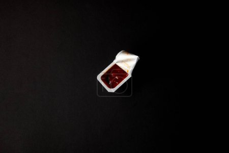 top view of plastic container with ketchup isolated on black