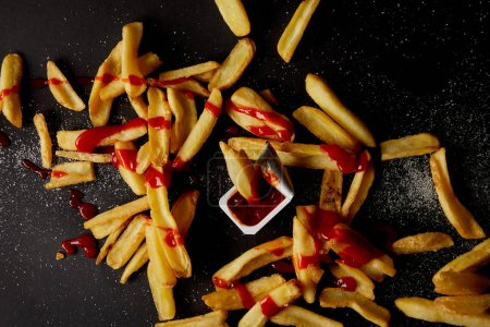 top view of french fries poured with ketchup and spilled with salt on black