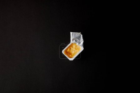 top view of plastic container with cheese sauce isolated on black