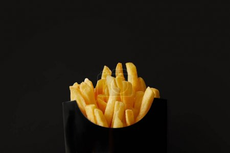close-up shot of black box of delicious french fries isolated on black