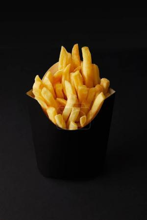 close-up shot of black box of tasty french fries isolated on black isolated on black