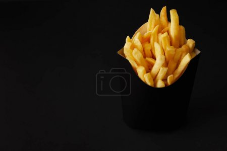 Photo for Black box of tasty french fries isolated on black isolated on black - Royalty Free Image
