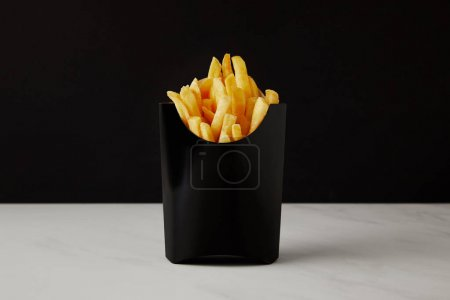box of french fries on white marble surface isolated on black