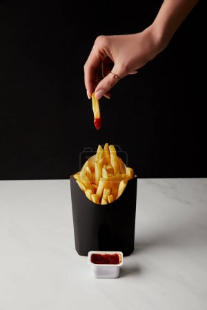 cropped shot of woman folding french fry poured into ketchup over box of fries isolated on black
