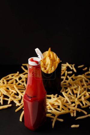bottle of ketchup with messy french fries on black surface isolated on black