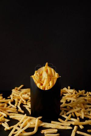 close-up shot of delicious french fries in black box surrounded with messy fries on tabletop isolated on black