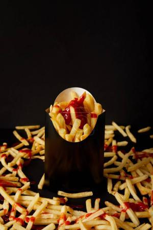 close-up shot of french fries in black box surrounded with messy fries on tabletop isolated on black