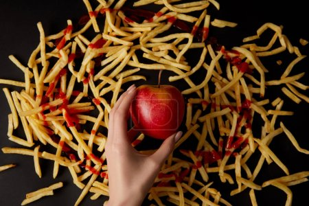 cropped shot of woman holding red apple surrounded with french fries isolated on black