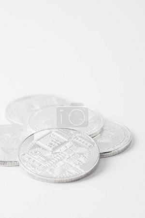 close-up shot of pile of bitcoins lying on white surface