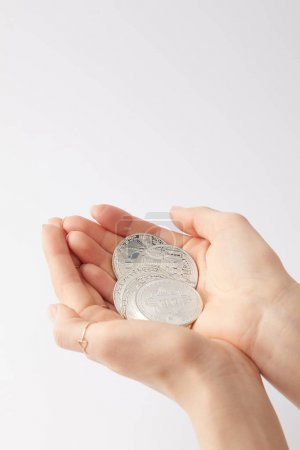 cropped shot of woman holding pile of bitcoins in hands isolated on white