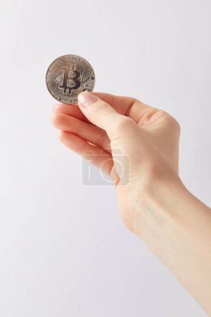 cropped shot of woman holding silver bitcoin isolated on white