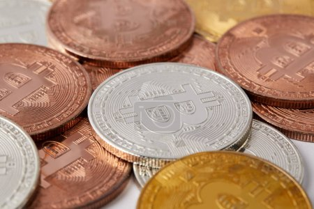 close-up shot shot of various bitcoins spilled on white surface
