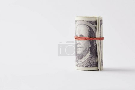 roll of dollars tied with rubber band on white tabletop