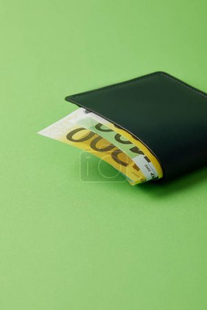 close-up shot of wallet with euro banknotes on green surface