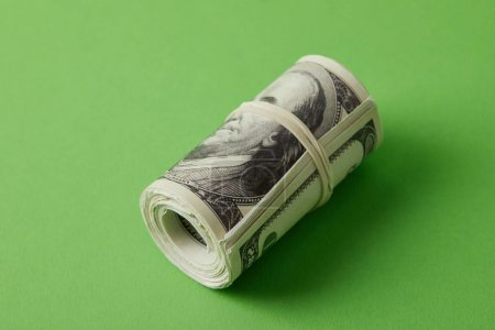 roll of dollars tied with rubber band on green surface