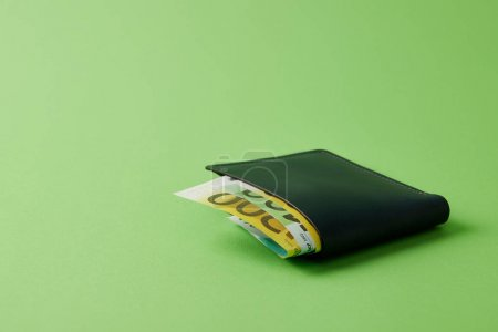 close-up shot of wallet with euro banknotes on green