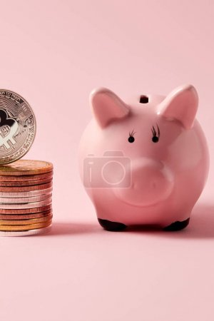 close-up shot of stack of bitcoins and piggy bank on pink tabletop