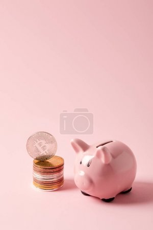 stack of bitcoins and piggy bank on pink tabletop