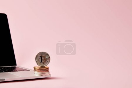 bitcoins stacked on laptop on pink surface