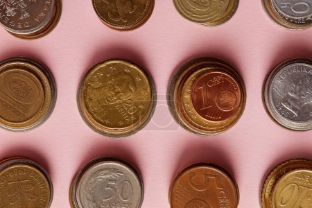 top view of stacks of coins from various countries on pink