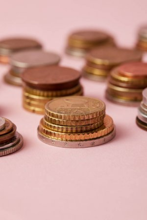 close-up shot of stacks of coins from various countries on pink