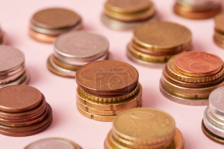 close-up shot of stacks of various coins on pink