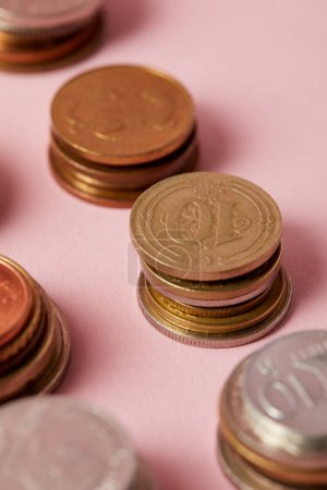 close-up shot of stacks of different coins on pink