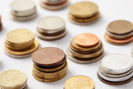 close-up shot of stacks of coins from various countries on white