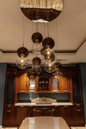 Shiny spherical chandelier over elegant wooden counter in kitchen