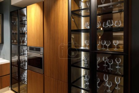 Interior of modern kitchen with glasses in cupboard