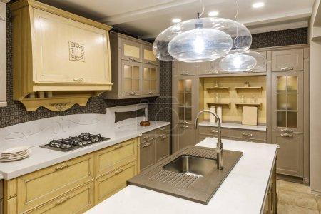 Stylish kitchen with chandelier over modern sink