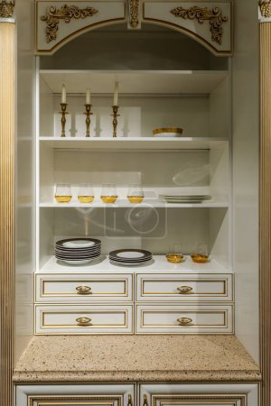 Interior of modern kitchen with elegant tableware in cupboard